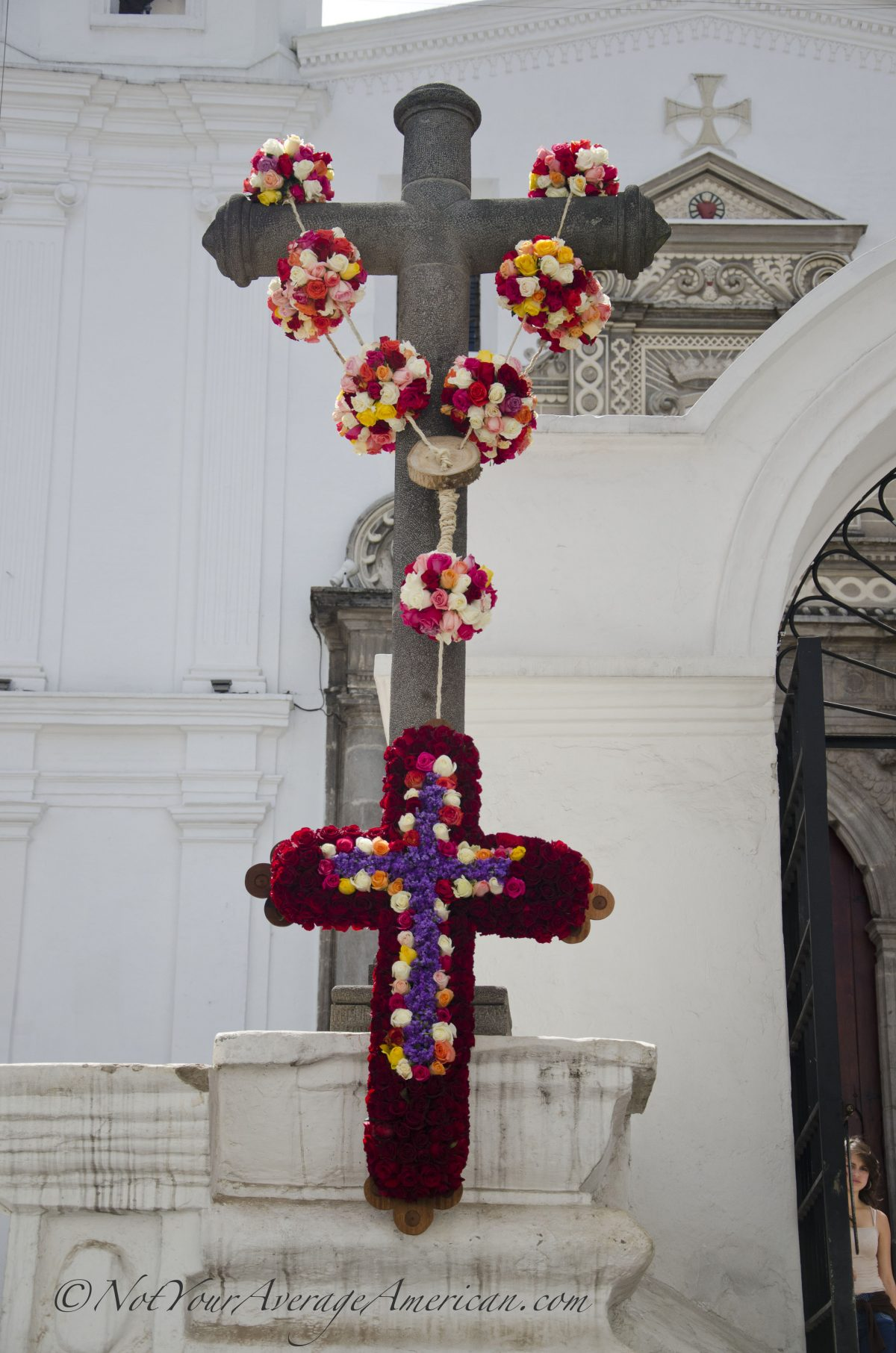 The rose draped cross in the afternoon light in front of the Convento del Carmen Alto | ©Angela Drake