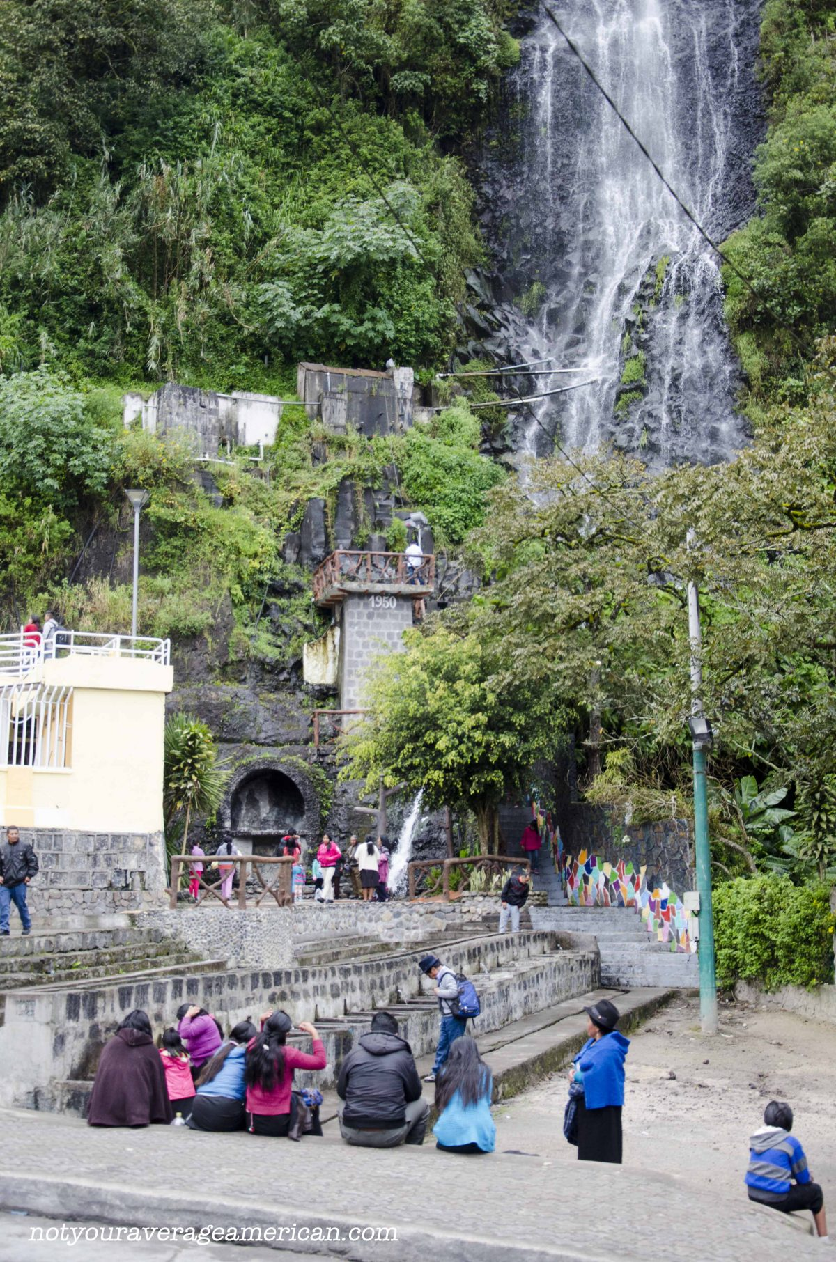 Visitors sitting at the base of La Cabellera de la Virgin (the Virgin's Tresses) in Baños, Ecuador.