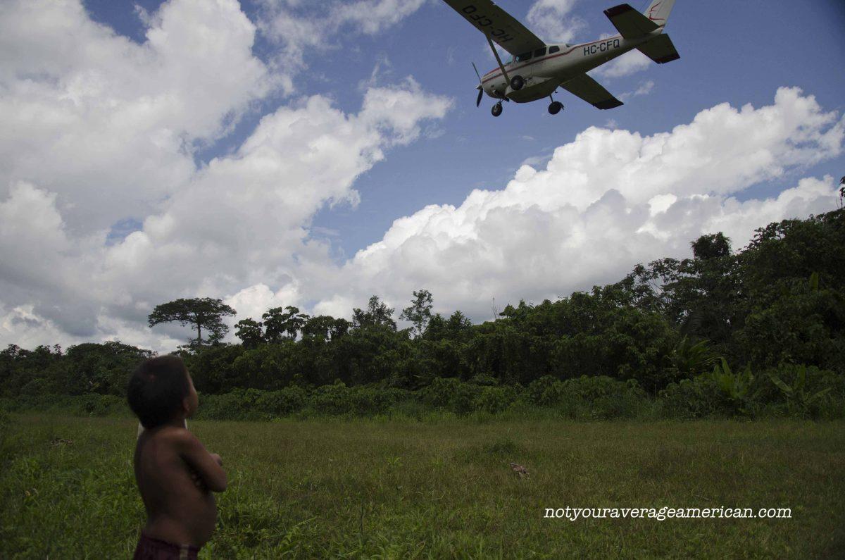 A Huaorani child watches as Alas de Socorro takes off, Huaorani Lodge