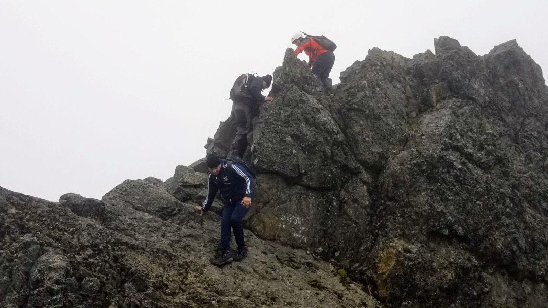 Un excursionista ayuda a otro a subir a la cima del Rucu Pichincha