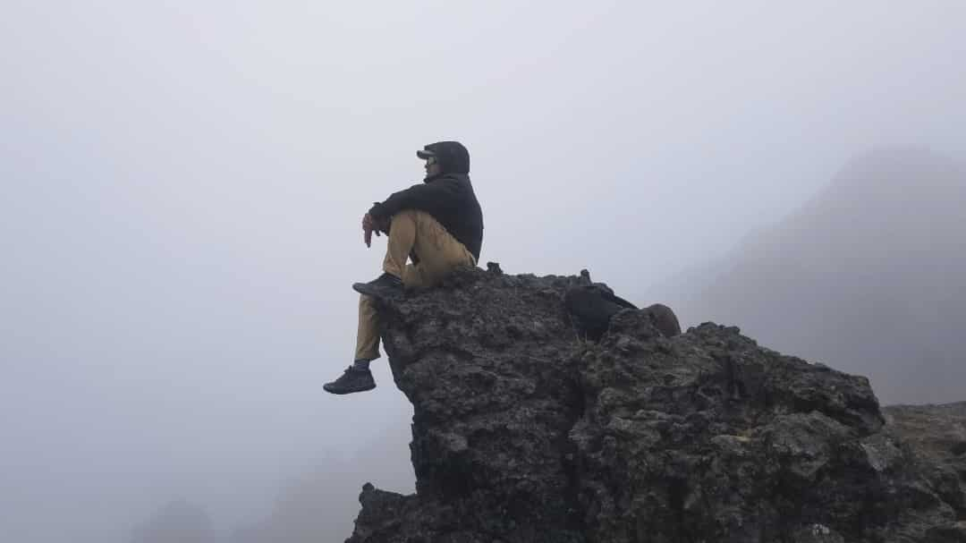 El autor sentado en la punta de una cresta con vistas a la niebla